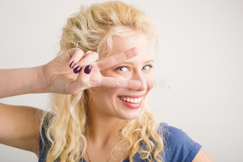 Ευτυχές κορίτσι που κρατά δύο δάχτυλα μπροστά από το πρόσωπό της στοκ εικόνα με δικαίωμα ελεύθερης χρήσης