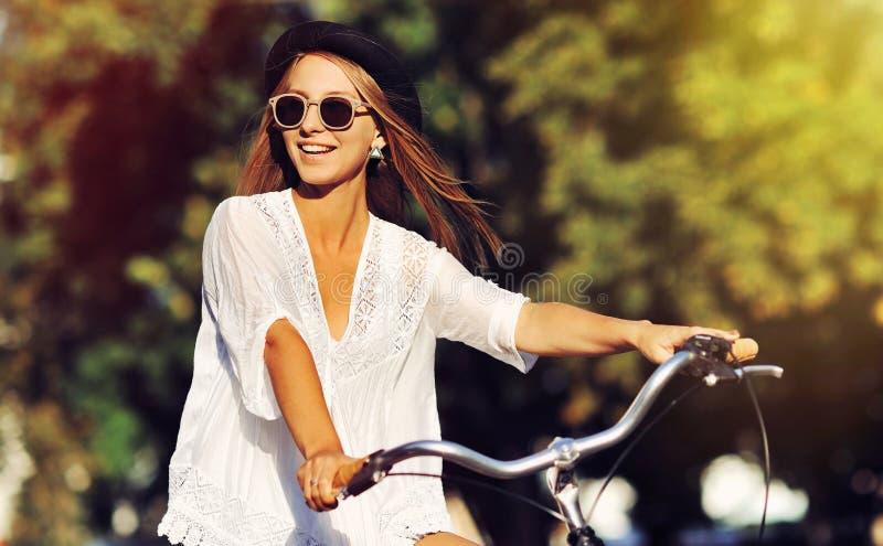 Ευτυχές κορίτσι που οδηγά ένα bycicle - υπαίθριο θερινό πορτρέτο στοκ εικόνα