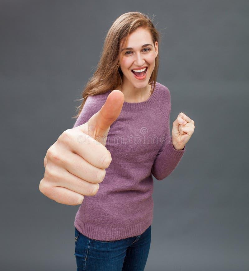 Ευτυχές κορίτσι που παρουσιάζει μεγάλους αντίχειρες με την πρόθυμη γλώσσα του σώματος στοκ φωτογραφία