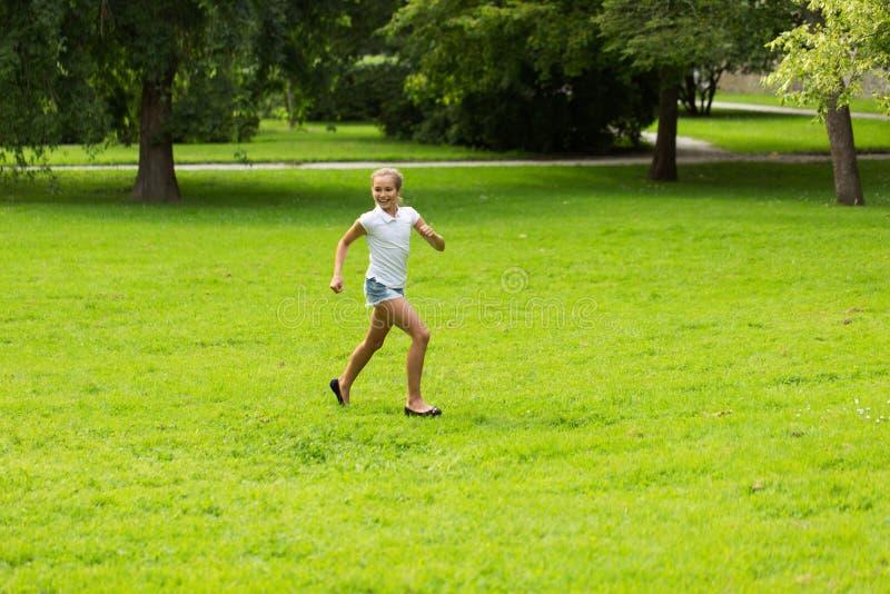 Ευτυχές κορίτσι που τρέχει και που παίζει στο καλοκαίρι υπαίθρια στοκ φωτογραφία με δικαίωμα ελεύθερης χρήσης