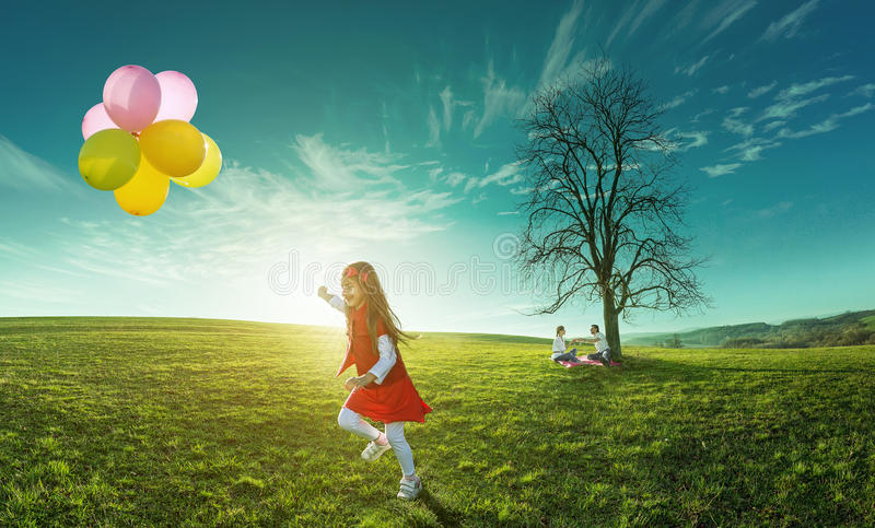 Ευτυχές κορίτσι που τρέχει σε ένα λιβάδι με τα μπαλόνια στοκ φωτογραφία
