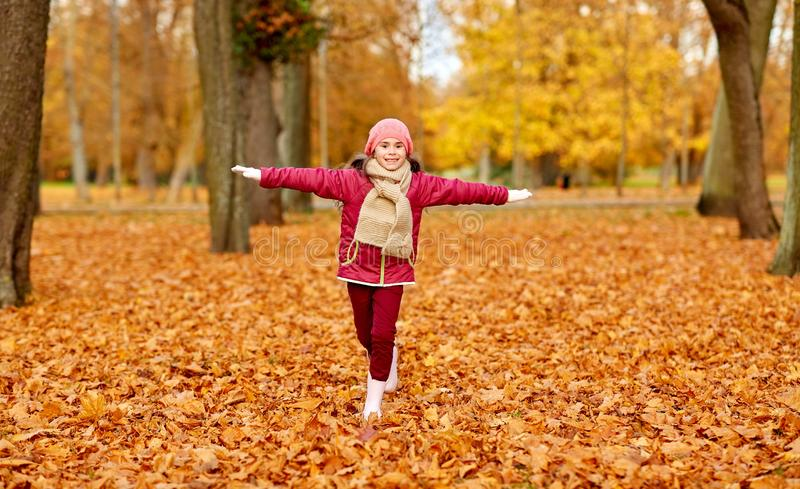 Ευτυχές κορίτσι που τρέχει στο πάρκο φθινοπώρου στοκ φωτογραφίες