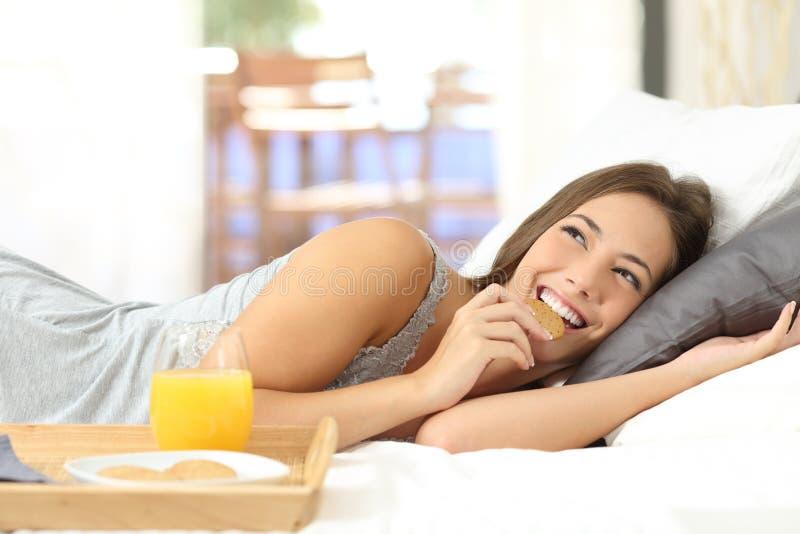 Ευτυχές κορίτσι που τρώει τα διαιτητικά μπισκότα στο πρόγευμα στοκ εικόνες
