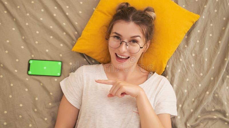 Ευτυχές κορίτσι που χρησιμοποιεί το smartphone που βρίσκεται στο κρεβάτι στο σπίτι στοκ φωτογραφία