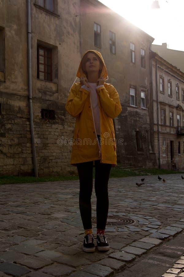 Ευτυχές κορίτσι σε ένα κίτρινο αδιάβροχο στοκ εικόνες
