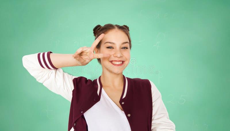 Ευτυχές κορίτσι σπουδαστών που παρουσιάζει σημάδι ειρήνης πέρα από πράσινο στοκ εικόνα