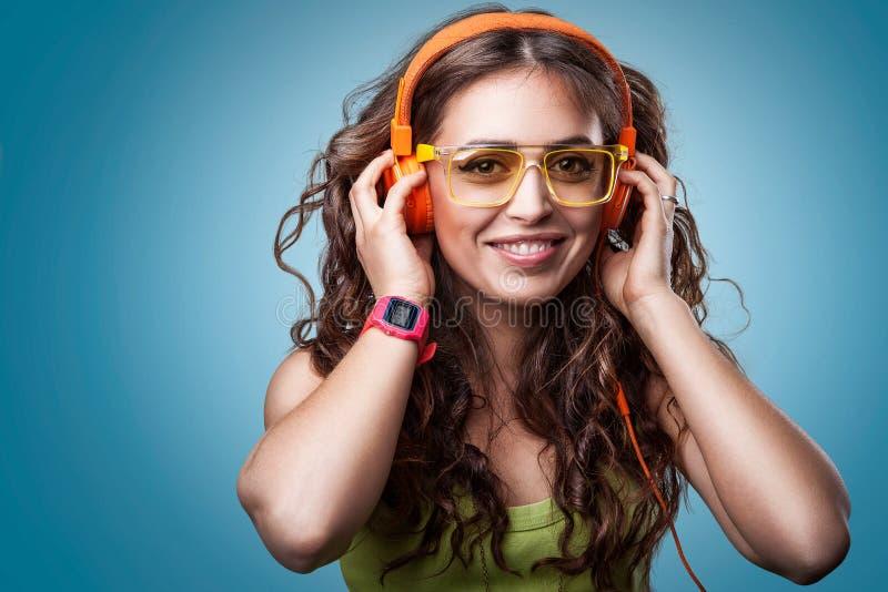Ευτυχές κορίτσι στα ακουστικά που ακούει τη μουσική στοκ εικόνα