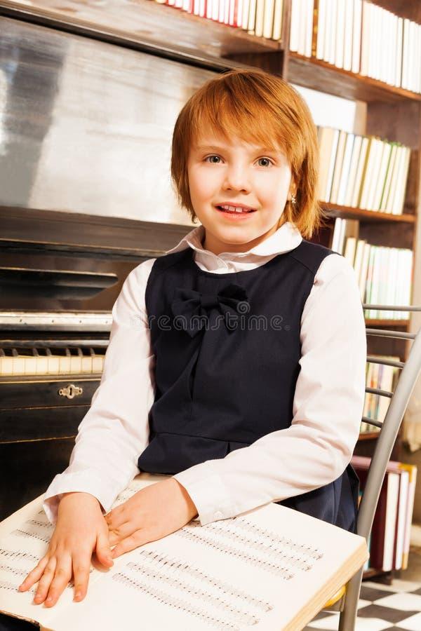 Ευτυχές κορίτσι στις σημειώσεις πιάνων εκμετάλλευσης σχολικών στολών στοκ φωτογραφίες με δικαίωμα ελεύθερης χρήσης