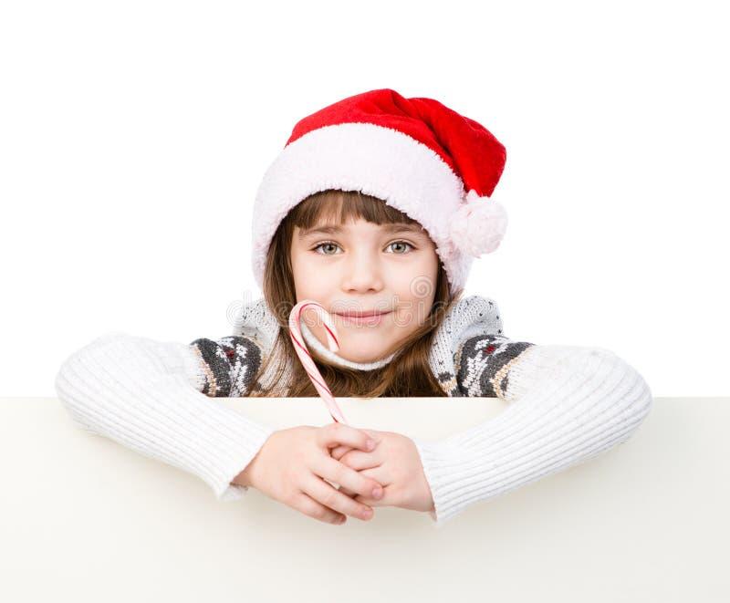 Ευτυχές κορίτσι στο καπέλο santa με τον κάλαμο καραμελών Χριστουγέννων που στέκεται πίσω από το έμβλημα Απομονωμένος στο λευκό στοκ φωτογραφίες