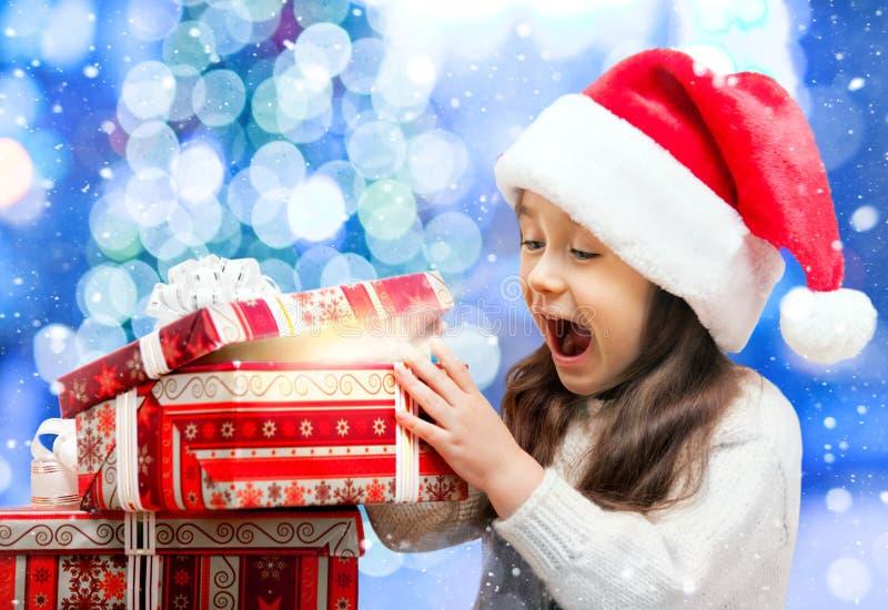 Ευτυχές κορίτσι στο καπέλο Santa που ανοίγει ένα κιβώτιο δώρων στοκ φωτογραφίες