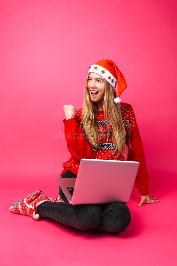 Ευτυχές κορίτσι στο κόκκινα πουλόβερ και το καπέλο Santa, που διεγείρονται για το αγαθό στοκ φωτογραφίες με δικαίωμα ελεύθερης χρήσης