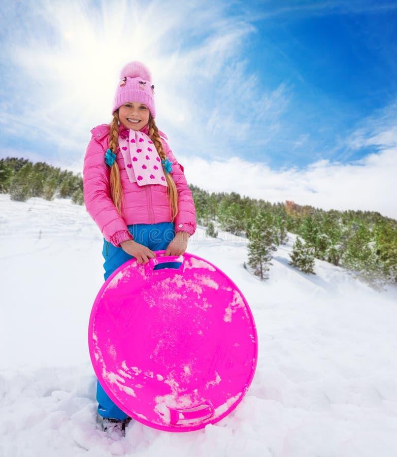 Ευτυχές κορίτσι στο ρόδινο έλκηθρο εκμετάλλευσης στοκ φωτογραφία