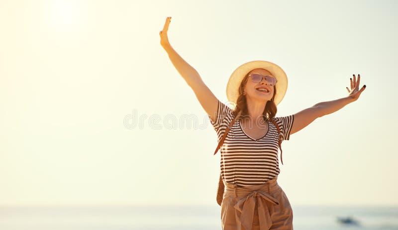 Ευτυχές κορίτσι τουριστών με το σακίδιο πλάτης και καπέλο στη θάλασσα στοκ φωτογραφίες