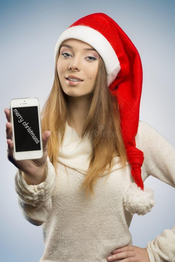 Ευτυχές κορίτσι Χριστουγέννων που παρουσιάζει smartphone στοκ φωτογραφία