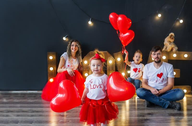 Ευτυχές κοριτσάκι με τα μπαλόνια καρδιών και η οικογένειά της που έχει τη διασκέδαση την ημέρα του βαλεντίνου Αγίου στοκ εικόνες με δικαίωμα ελεύθερης χρήσης