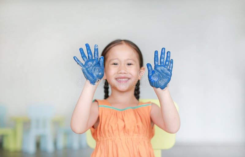 Ευτυχές λίγο ασιατικό κορίτσι με το μπλε της παραδίδει το χρώμα στο δωμάτιο παιδιών Εστίαση στα χέρια μωρών στοκ φωτογραφίες με δικαίωμα ελεύθερης χρήσης