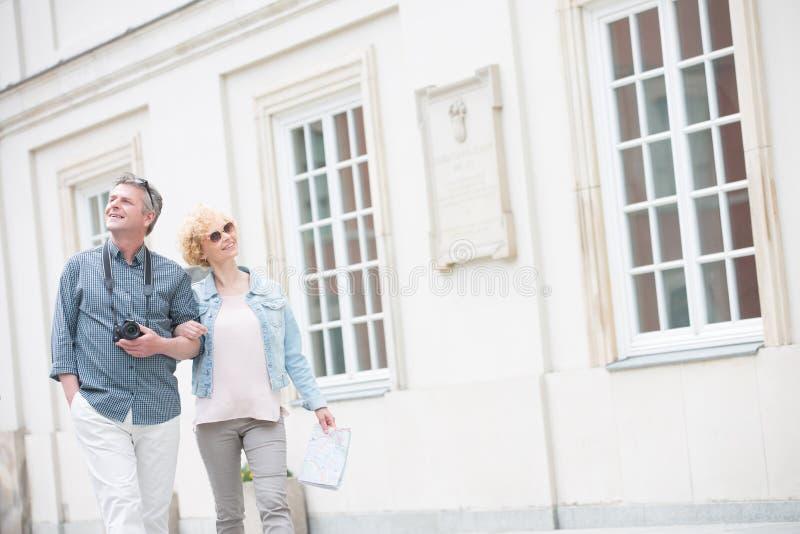 Ευτυχές μέσης ηλικίας αγκαζέ περπατήματος ζευγών τουριστών με την οικοδόμηση στοκ φωτογραφία