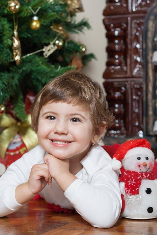 Ευτυχές μικρό κορίτσι κοντά στο χριστουγεννιάτικο δέντρο στοκ εικόνα με δικαίωμα ελεύθερης χρήσης