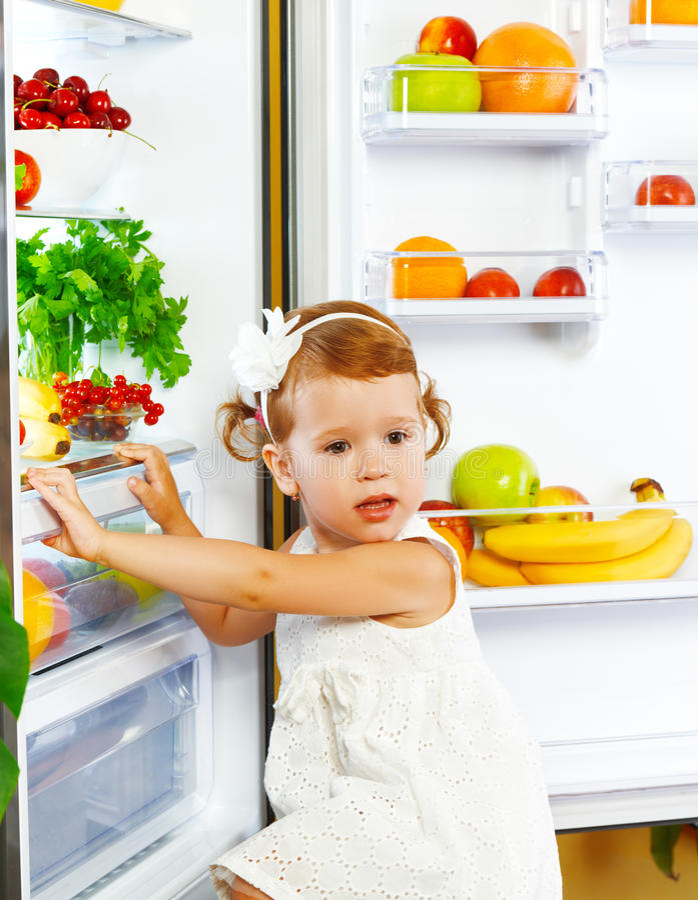 Ευτυχές μικρό κορίτσι κοντά στο ψυγείο με τα υγιή τρόφιμα, φρούτα και στοκ εικόνες με δικαίωμα ελεύθερης χρήσης