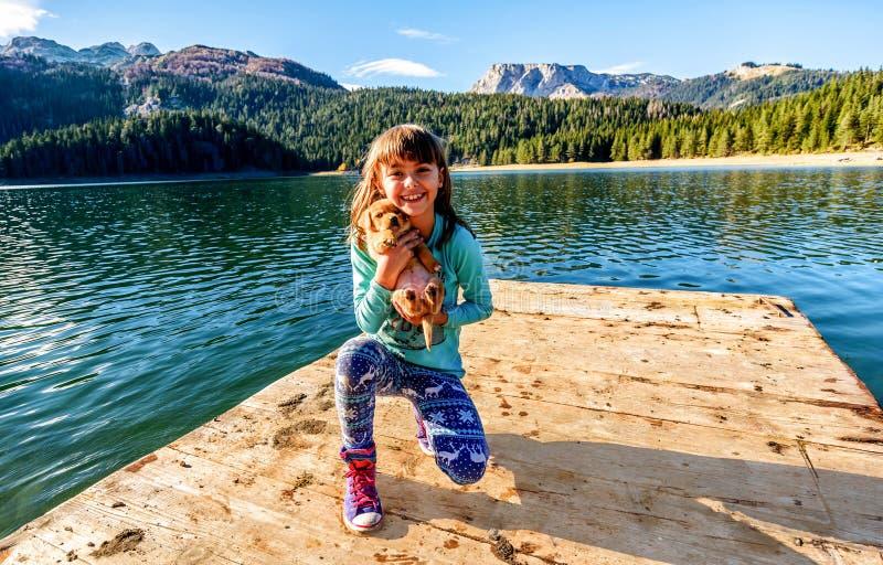 Ευτυχές μικρό κορίτσι με ένα κουτάβι από τη μαύρη λίμνη (jezero Crno), στοκ εικόνες