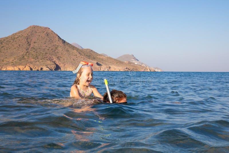 Ευτυχές μικρό κορίτσι με τα γυαλιά κατάδυσης στην πλάτη της γυναίκας που κολυμπά με αναπνευτήρα στο νερό μιας παραλίας στην Ανδαλ στοκ φωτογραφία