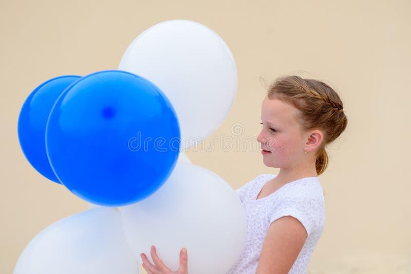 Ευτυχές μικρό κορίτσι με τα μπλε και άσπρα μπαλόνια στοκ εικόνα