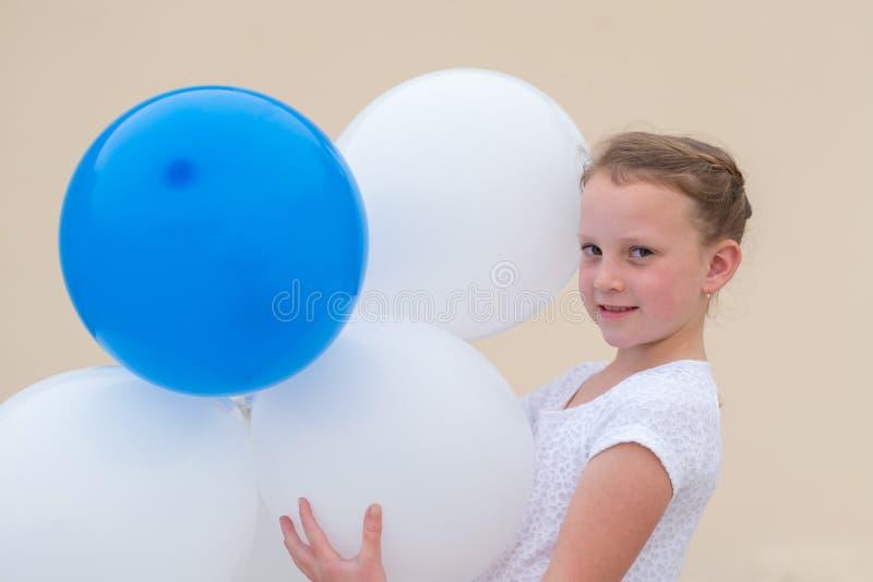 Ευτυχές μικρό κορίτσι με τα μπλε και άσπρα μπαλόνια στοκ φωτογραφία με δικαίωμα ελεύθερης χρήσης