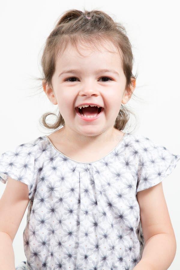 ευτυχές μικρό κορίτσι με την εξέταση χαμόγελου γέλιου φορεμάτων τη κάμερα στοκ φωτογραφία