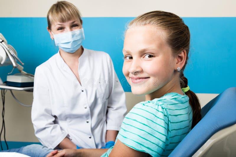 Ευτυχές μικρό κορίτσι με το ανοικτό στόμα που υποβάλλεται στην οδοντική επεξεργασία στην κλινική Οδοντίατρος που ελέγχεται και πο στοκ φωτογραφία με δικαίωμα ελεύθερης χρήσης