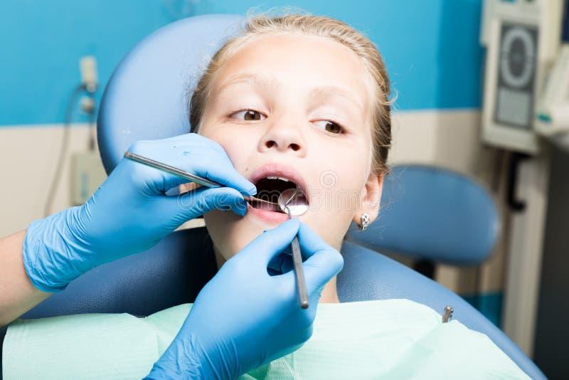 Ευτυχές μικρό κορίτσι με το ανοικτό στόμα που υποβάλλεται στην οδοντική επεξεργασία στην κλινική Οδοντίατρος που ελέγχεται και πο στοκ φωτογραφία
