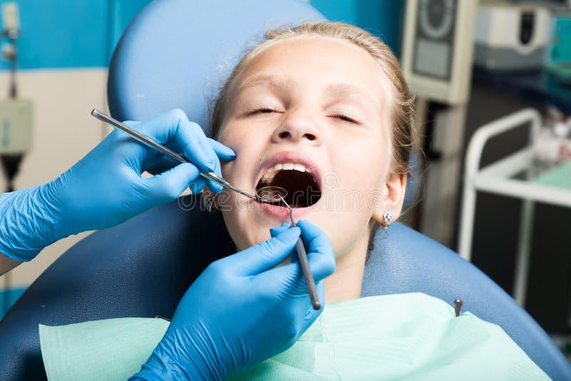 Ευτυχές μικρό κορίτσι με το ανοικτό στόμα που υποβάλλεται στην οδοντική επεξεργασία στην κλινική Οδοντίατρος που ελέγχεται και πο στοκ φωτογραφίες
