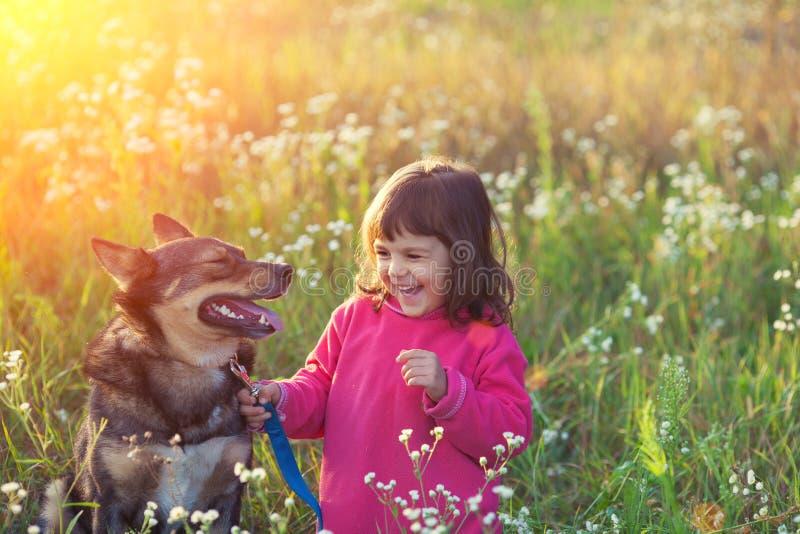 Ευτυχές μικρό κορίτσι με το σκυλί στοκ εικόνα