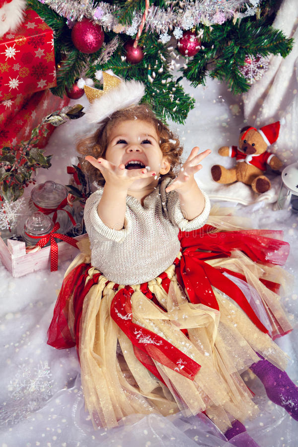 Ευτυχές μικρό κορίτσι μπροστά από το χριστουγεννιάτικο δέντρο στοκ εικόνα
