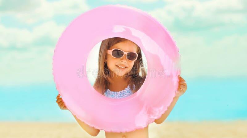 Ευτυχές μικρό κορίτσι παιδιών κινηματογραφήσεων σε πρώτο πλάνο πορτρέτου που κρατά το διογκώσιμο λαστιχένιο κύκλο που έχει τη δια στοκ φωτογραφίες με δικαίωμα ελεύθερης χρήσης