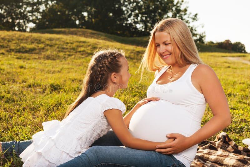 Ευτυχές μικρό κορίτσι που αγκαλιάζει την έγκυος κοιλιά της μητέρας στοκ φωτογραφία με δικαίωμα ελεύθερης χρήσης