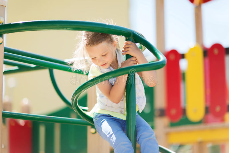 Ευτυχές μικρό κορίτσι που αναρριχείται στην παιδική χαρά παιδιών στοκ φωτογραφία με δικαίωμα ελεύθερης χρήσης