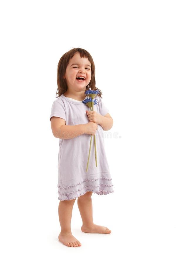 Ευτυχές μικρό κορίτσι με τα λουλούδια στοκ φωτογραφίες