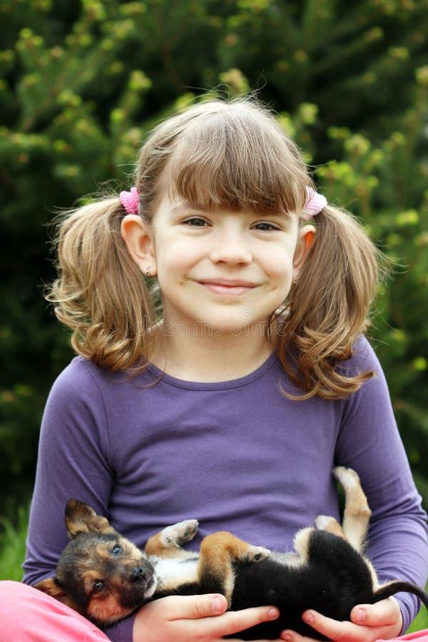 Ευτυχές μικρό κορίτσι που κρατά το χαριτωμένο κουτάβι στοκ φωτογραφίες