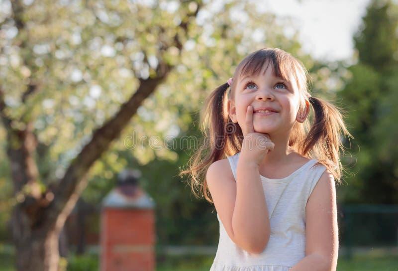 Ευτυχές μικρό κορίτσι που ονειρεύεται στον κήπο στοκ εικόνες