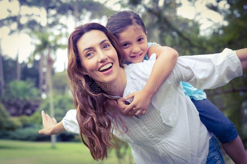 Ευτυχές μικρό κορίτσι που παίρνει ένα σηκώνω στην πλάτη από τη μητέρα στο πάρκο στοκ φωτογραφία με δικαίωμα ελεύθερης χρήσης