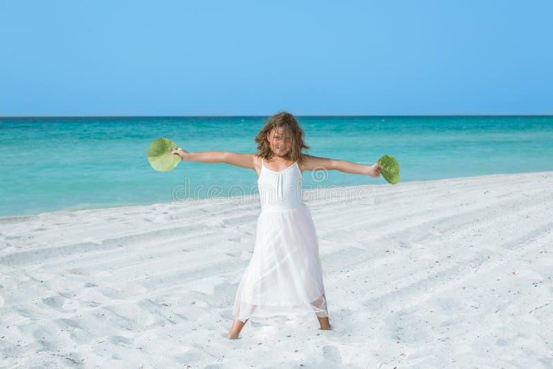 Ευτυχές μικρό κορίτσι που στέκεται στην άσπρη τροπική παραλία άμμου στοκ εικόνες με δικαίωμα ελεύθερης χρήσης