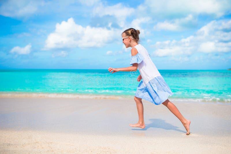 Ευτυχές μικρό κορίτσι που τρέχει και που καταβρέχει στα ρηχά νερά στην παραλία που έχει πολλή διασκέδαση στις διακοπές στοκ φωτογραφία με δικαίωμα ελεύθερης χρήσης