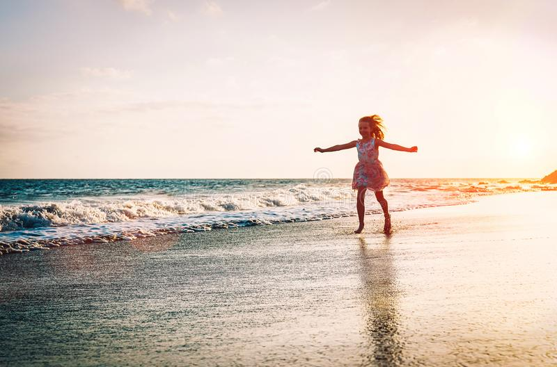 Ευτυχές μικρό κορίτσι που τρέχει το εσωτερικό νερό που διαδίδει τα χέρια της επάνω στην παραλία - μωρό που έχει τη διασκέδαση που στοκ εικόνες με δικαίωμα ελεύθερης χρήσης