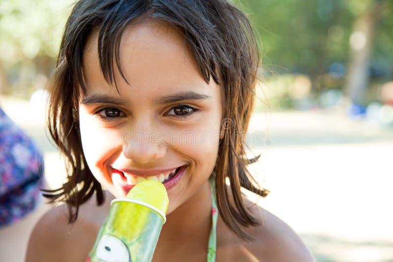 Ευτυχές μικρό κορίτσι που τρώει ένα παγωτό μετά από να κολυμπήσει στοκ φωτογραφίες