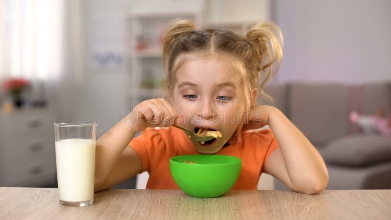Ευτυχές μικρό κορίτσι που τρώει τα δημητριακά με τον εγχώριο πίνακα συνεδρίασης γάλακτος, υγιή τρόφιμα στοκ φωτογραφία