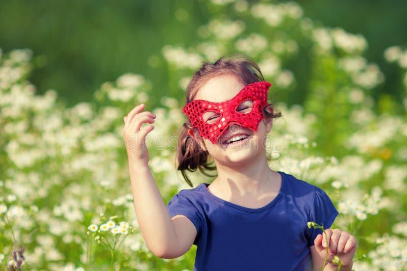Ευτυχές μικρό κορίτσι που φορά μια κόκκινη μάσκα στοκ εικόνα με δικαίωμα ελεύθερης χρήσης