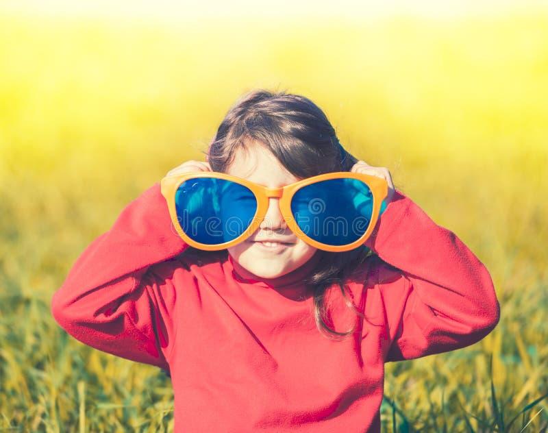Ευτυχές μικρό κορίτσι που φορά τα μεγάλα γυαλιά ηλίου στοκ εικόνα με δικαίωμα ελεύθερης χρήσης
