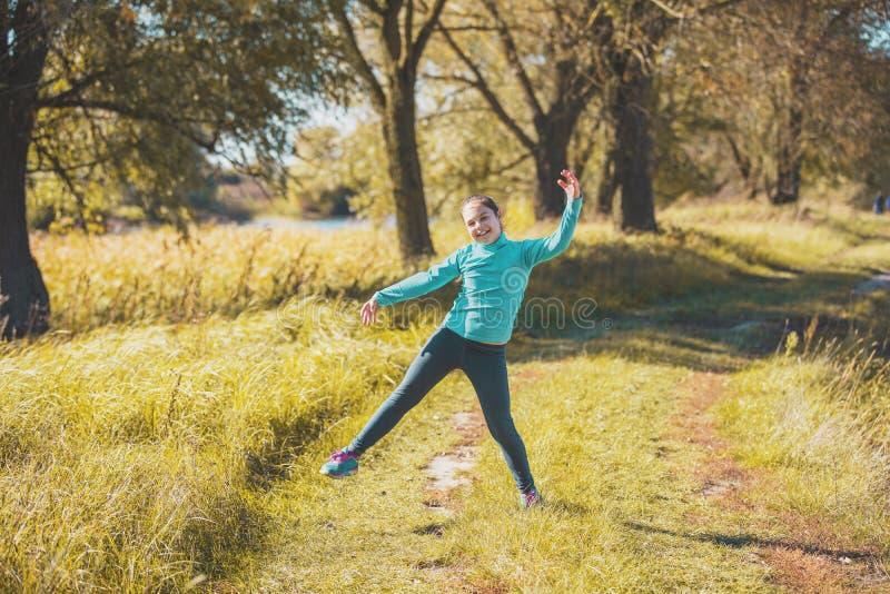 Ευτυχές μικρό κορίτσι που χορεύει στον αγροτικό δρόμο στοκ φωτογραφίες