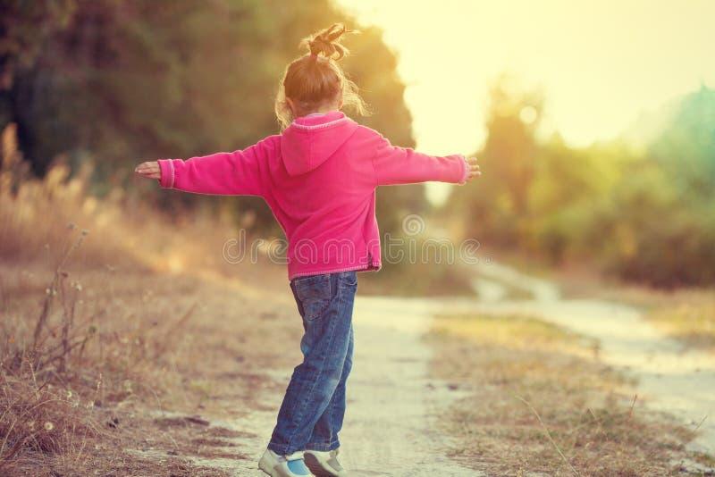 Ευτυχές μικρό κορίτσι που χορεύει στον αγροτικό δρόμο στοκ εικόνα με δικαίωμα ελεύθερης χρήσης