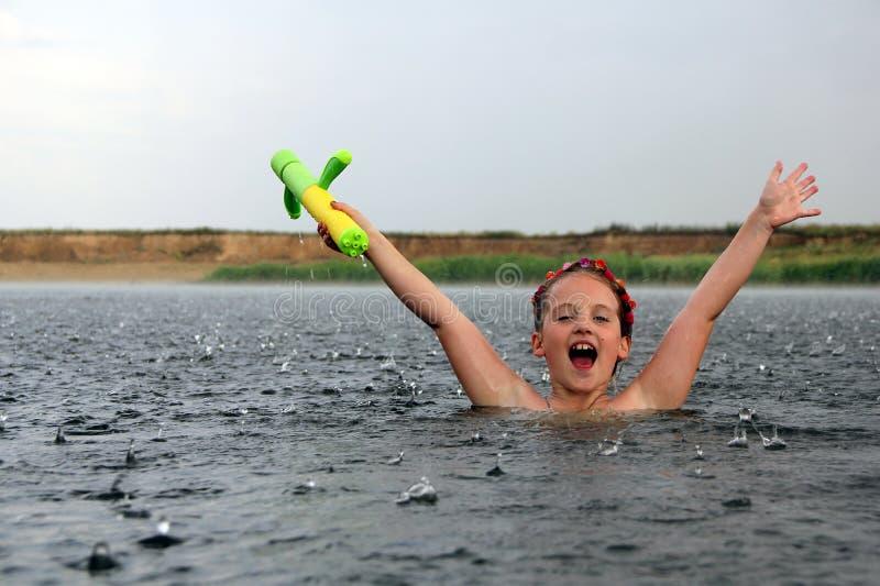 ευτυχές μικρό κορίτσι σε έναν ποταμό κάτω από τη βροχή στοκ εικόνες